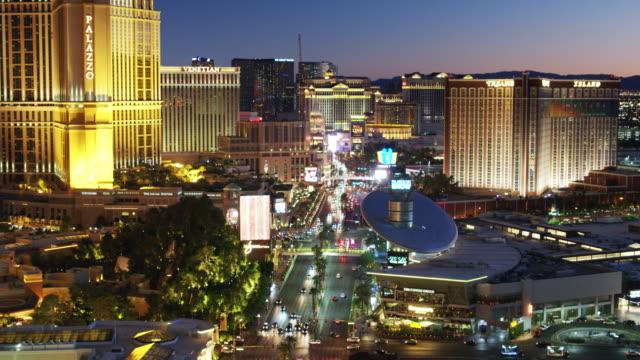 the las vegas strip lit up after sunset - drone shot - the strip las vegas stock-videos und b-roll-filmmaterial