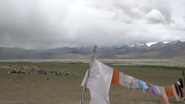 vídeos de stock, filmes e b-roll de the laundry of local people with the tso kar lake and himalayas in the back, rupshu plateau, ladakh, india. - secar