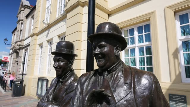 the laurel and hardy statue outside the coronation hall in ulverston, cumbria, uk. stan laurel was born in ulverston. the statue was designed and... - comedian stock videos & royalty-free footage