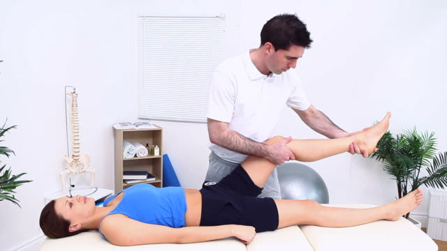 the leg of a woman being stretched by a physiotherapist - ligament stock videos and b-roll footage