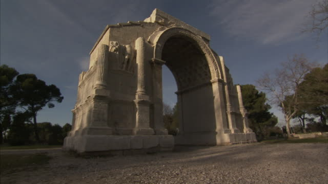 The Les Antiques Triumphal Arch frames a cloudy sky at Saint Remy de Provence in France.