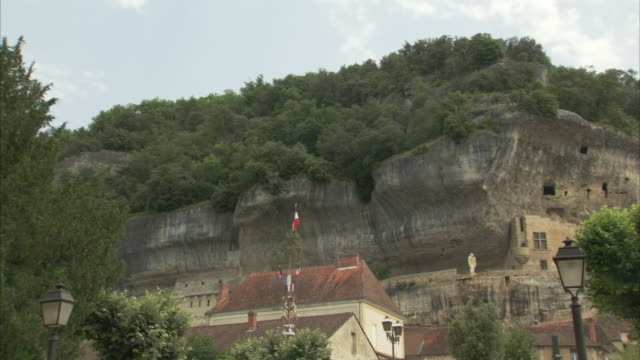 stockvideo's en b-roll-footage met the les eyzies caves cut into a mountain in france. - rotsmuur