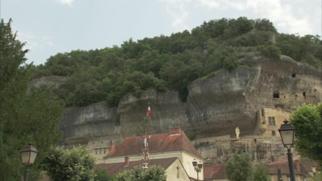 vídeos de stock e filmes b-roll de the les eyzies caves cut into a mountain in france. - paredão rochoso