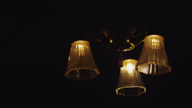 the light bulbs in a vintage hanging ceiling light fixture are switched on and off. - 吊り照明点の映像素材/bロール