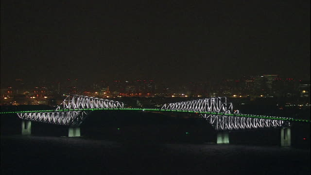 the lighted tokyo skyline reflects behind the tokyo gate bridge. - cantilever stock videos & royalty-free footage
