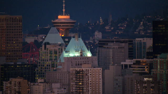 The lighted tops of the Hotel Vancouver and Harbour Centre peek out atop the Vancouver skyline.