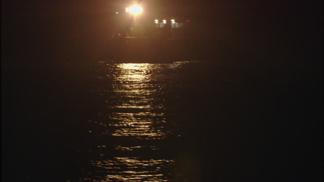 the lights of a fishing boat illuminate dark waters. - nautical vessel stock videos & royalty-free footage