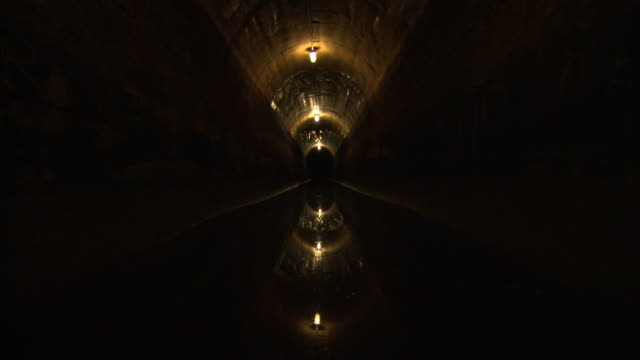 the lights of a sewage tunnel shine over sewage in new york city. - sewage stock videos and b-roll footage