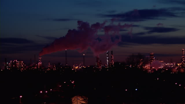 The lights of an oil refinery twinkle as smoke pours from a smokestack in Linden, New Jersey, at night.
