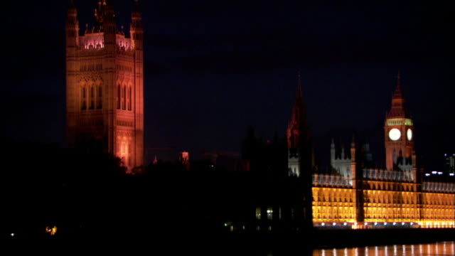 the lights of london's westminster abbey, the houses of parliament, and big ben reflect on the river thames at night. - westminster abbey stock videos & royalty-free footage