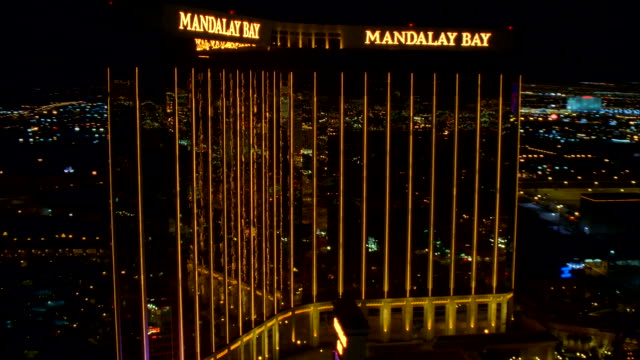 the lights of the las vegas strip reflect off the windows of the mandalay bay hotel. available in hd. - mandalay bay resort and casino stock videos & royalty-free footage