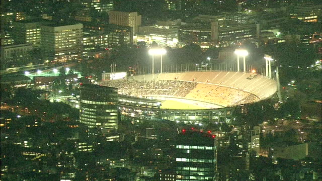 the lights of the national stadium in tokyo stand out among the city lights at night / national stadium in tokyo is the symbolic venue of the 1964... - summer olympic games stock videos and b-roll footage