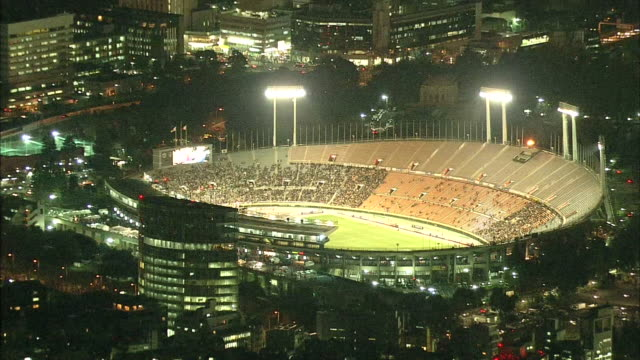 the lights of the national stadium in tokyo stand out among the city lights at night. / national stadium in tokyo is the symbolic venue of the 1964... - hitting stock videos & royalty-free footage