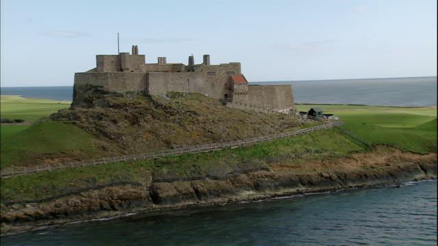 The Lindisfarne Castle overlooks rippling water on Holy Island, Northumberland, England.