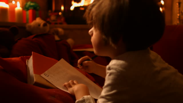 the little boy writes a letter to santa - letter stock videos and b-roll footage
