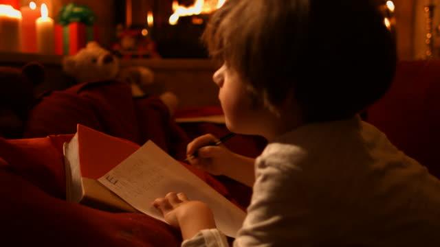 vídeos de stock e filmes b-roll de o rapaz a escrever uma carta ao pai - mensagem