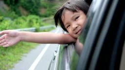 The little child feels refreshed with the tourist atmosphere by car.