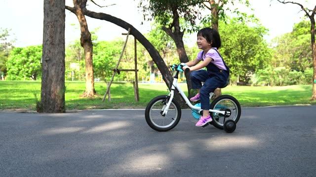 das kleine mädchen auf dem fahrrad in einem sonnigen park. vorschulkinder lernen, auf dem fahrrad auszubalancieren. - motorradfahrer stock-videos und b-roll-filmmaterial