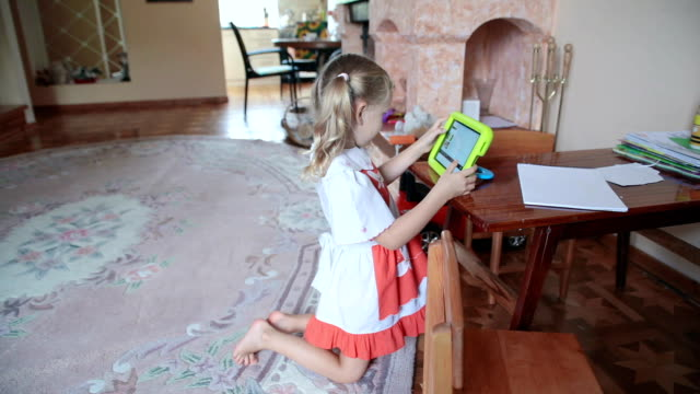 the little girl uses her tablet for fun. - digital native stock videos & royalty-free footage