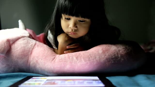 vidéos et rushes de la petite fille utilise la tablette pendant la nuit. - synthpop