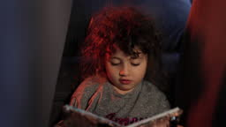 The little girl with curly hair is reading, The little girl is reading in the tent she has made from the armchairs, the little girl is spending time in her private space,