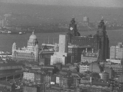 the liverpool port authority building and the royal liver building stand next to the river mersey 1964 - リバプール点の映像素材/bロール