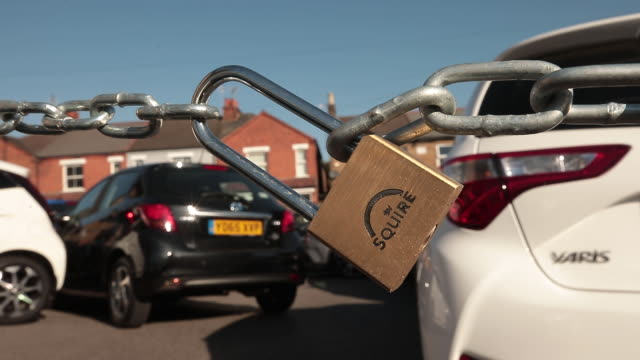 stockvideo's en b-roll-footage met the locked gate of a closed car dealership lot during the coronavirus lockdown in london, england, u.k. on monday, april 20, 2020. - toonzaal