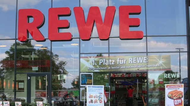 vidéos et rushes de the logo of rewe sits on banners flying outside a supermarket operated by rewe group in berlin, germany, on tuesday, april 29 the logo of rewe sits... - caddie