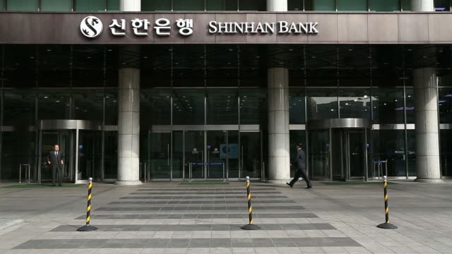 the logo of shinhan bank a unit of shinhan financial group co is displayed on a revolving door at the bank's headquarters in seoul south korea on... - 角度点の映像素材/bロール