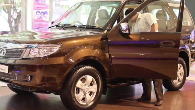 the logo of tata motors ltd is displayed on the front grill of a tata manza sedan automobile on display inside the prabhadevi concorde motors india... - safari india stock videos and b-roll footage