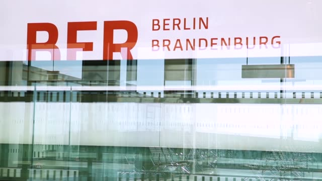 the logo of the ber willy brandt berlin brandenburg international airport is seen through the glass of a people mover inside the south pier terminal... - brandenburg state stock videos & royalty-free footage