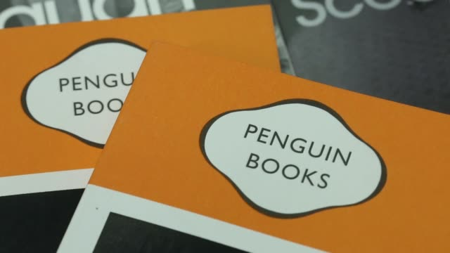 the logo of the penguin publishing house part of pearson plc is seen on paperback books at a bookstore in london close shot 'penguin books' logo on... - paperback stock videos & royalty-free footage