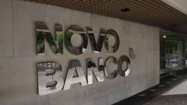 the logos of novo banco sa sit on display outside the companys headquarters in lisbon portugal on wednesday aug 12 2015 shots a former customer of... - 金融関係施設点の映像素材/bロール