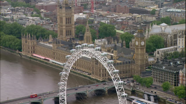 the london eye ferris wheel overlooks the houses of parliament in london, england. - government building stock videos and b-roll footage