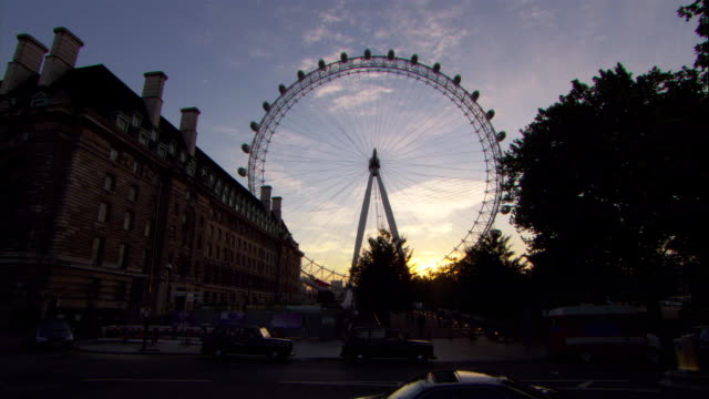 the london eye stands in silhouette against a deep blue sky. - big wheel stock videos & royalty-free footage