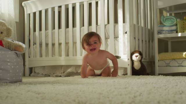 the long brown hair hangs in the eyes of a seven-month-old hispanic baby with brown eyes, very fussy, dressed only in a white diaper, sits, then crawls in front of his crib, toward camera. - ein männliches baby allein stock-videos und b-roll-filmmaterial