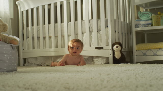 the long brown hair hangs in the eyes of a seven-month-old hispanic baby with brown eyes, dressed only in a white diaper, sits, then crawls in front of his crib, toward camera. - フェードアウト点の映像素材/bロール
