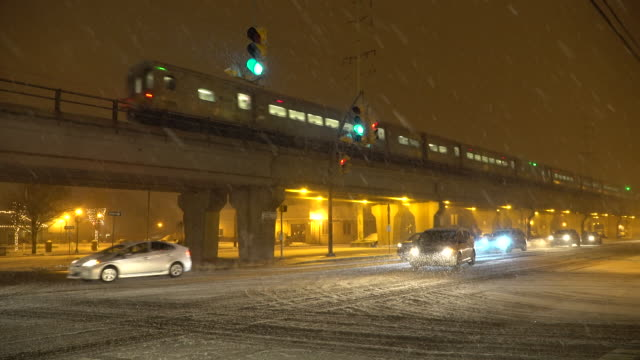 The Long Island Railroad runs express through Lindenhurst NY as vehicle traffic navigates slippery snow covered streets during a night time snow storm