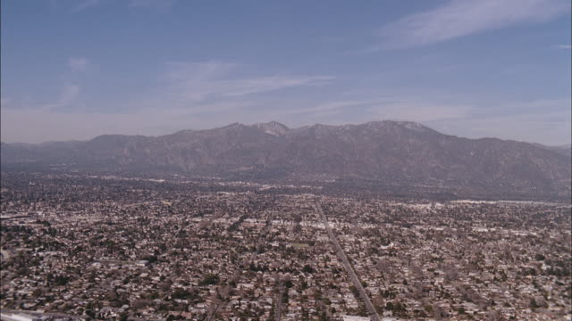 the los angeles cityscape sprawls to the base of a mountain. - valley stock videos & royalty-free footage