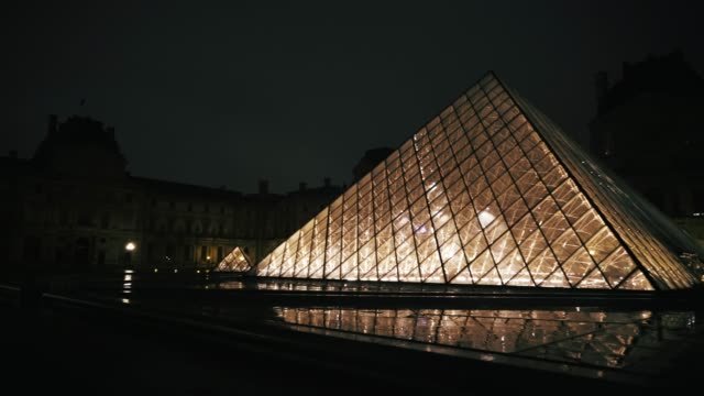 stockvideo's en b-roll-footage met the louvre pyramid is seen, at night under the rain, on march 15, 2019 in the 1st quarter of paris, france. - quarter