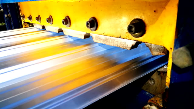 the machine cuts a sheet of metal. factory for the creation of metal roofing.manufacturing of metal profile for repairing the roof of the house. - metal plate stock videos & royalty-free footage