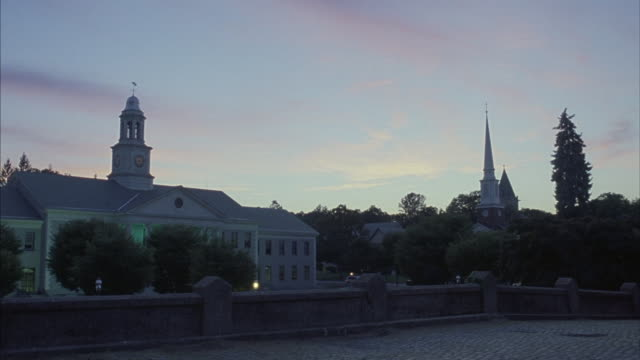 The Madison Town Hall stands beside a cobblestone bridge and a church.