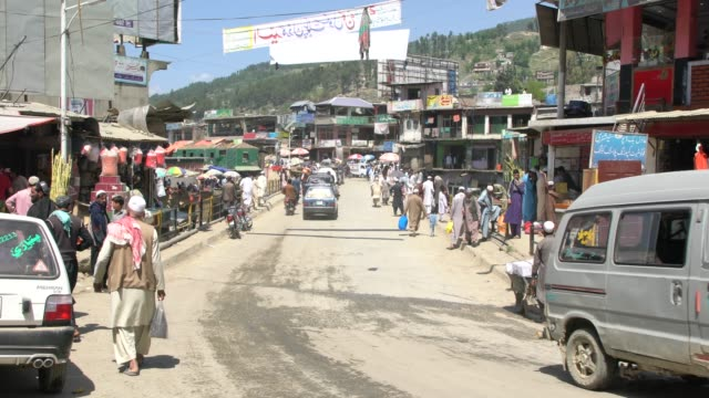 vídeos de stock e filmes b-roll de the main street alongside the busy market (bazar) in the muslim conservative town of battagram on the karakorum highway in northern pakistan - paquistão