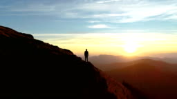 The male standing on the mountain and enjoying the picturesque sunset
