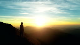 The male standing on the mountain and enjoying the sunset