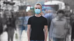 The male with medical face mask stands in the middle of urban space. time lapse