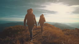 The man and woman walking along the mountain on a sunny background. slow motion