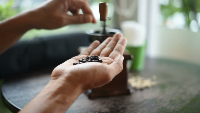 The man checked a coffee beans and put it in the coffee grinder.