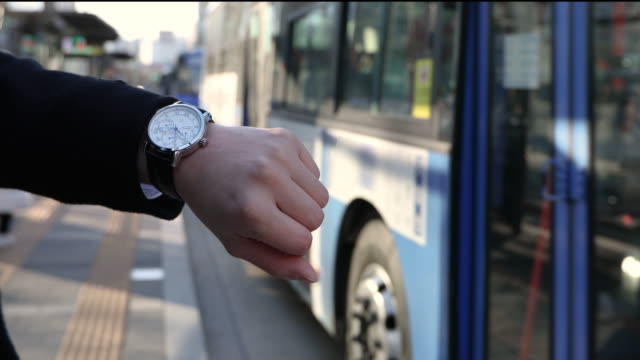 the man checking the time and waiting for the bus on the bus stop in seoul - wrist stock videos & royalty-free footage