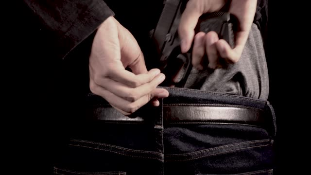 the man concealing gun behind his back - handgun stock videos and b-roll footage